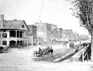 The Franklin County Bank is seen in this photo looking north up Main Street from Fairfield Street. The bank is the building with the rectangular sign on its side. The building to its left, with the elaborate porches, is the American House. It was on the sidewalk in front of it that Bennett Young signaled the start of the raid. At right is the park where residents were held hostage