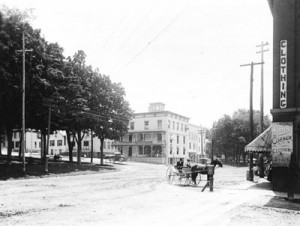 The First National Bank is visible in the distance on Fairfield Street. It is just behind where the men are seated on the bench in the park.