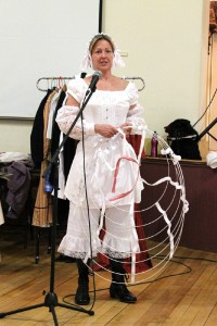 Lynn Sawyer, stripped down to just her undergarments and corset, shows the audience how to put on a hoop skirt. The skirts helped achieve the era's desired hourglass figure, as did dropped shoulders and oversize sleeves.