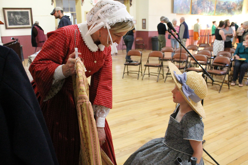 Mackenzie Smith, 6, models Civil War-era clothes as Lynn Sawyer from historic preservation group the Vermont 18th Regiment describes fashion trends popular at that time. In September 2014 folks will don period-appropriate clothing to participate in commemoration events for the 150th anniversary of the St. Albans Raid.